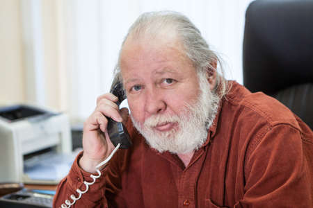 Decisive senior manager holding telephone handset and calling in office room, white beard and grey hair, looking at camera Standard-Bild - 119429823