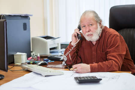Portrait of white bearded senior businessman using telephone, calling to somebody while working in office room Standard-Bild - 119429824