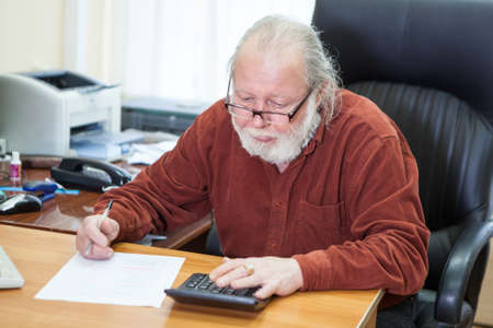 Mathematician senior man calculating and writing at the table at workplace, male sitting in leather chair Imagens - 119429825
