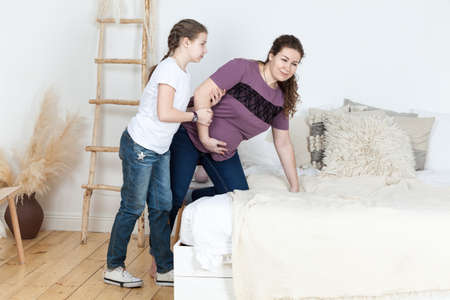 Teen Caucasian daughter assistances her pregnant mother to lie down on the bed, abdominal pain, domestic bedroom Standard-Bild - 119429826