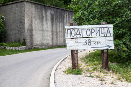 Wooden signpost with direction and distance to Podgorica city in countryside on rural asphalt road. Montenegro. Podgorica inscription in Montenegrin Standard-Bild - 119431616