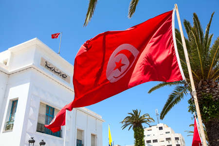 Red Tunisian national flag waves against administrative building in Sousse city. All government buildings must have flags on facade. Tunisia, the Africa Standard-Bild - 119431631