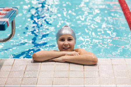 Ten years Caucasian girl swimmer standing in swimming pool, looking at camera and smiling Standard-Bild - 121327907
