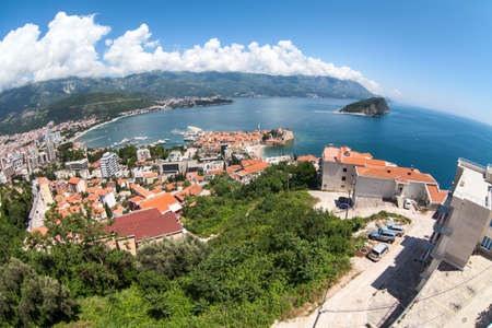 The city of Budva with the old town with fortified walls and red roofs. View from above, wide angle. Montenegro, Europe Standard-Bild - 121328076