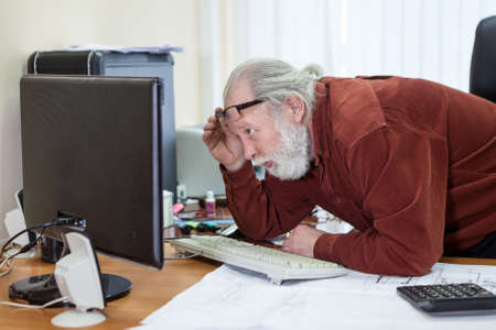 Retirement office employee looks at the monitor screen, lifting his glasses on his forehead and moving closer Stockfoto