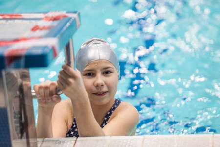 Girl child swimmer in a grey cap hanging on rails of starting stand of a swimming pool Standard-Bild - 121328253