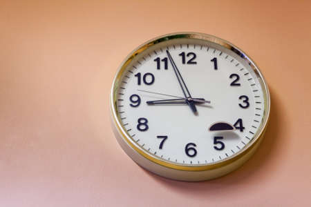 Round clock hanging on the pink wall. Time is now five minutes to nine. Copyspace