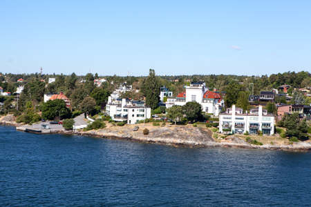 Many different building and houses are on coastline of Stockholm archipelago in Sweden. Joint valley landscape. Scandinavia, Europe Standard-Bild - 121328392