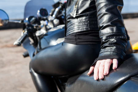 Woman motorcyclist dressed black leather outfit and leggins sitting on bike seat, looking behind, focus on hand Standard-Bild - 121328395