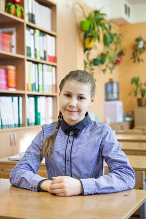 Portrait of Caucasian schoolgirl sitting at table in class, looking at camera