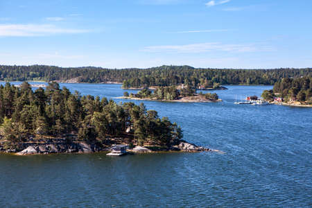 Rugged nature with wooded islands and rocky cliffs in Stockholm archipelago. Uninhabited islets, communities and ancient village with houses and small cottages. Sweden Standard-Bild - 121328393