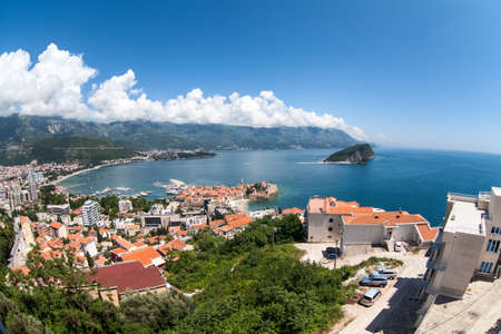 Panorama of Budva Riviera with city, old town with fortified walls and red roofs. View from above, wide angle. Adriatic sea, Balkans, Montenegro, Europe Standard-Bild - 121328525