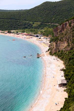 Coastline with Jaz beach in Budva municipality in Montenegro. Parasols with sun beds are on Adriatic sea shore, Balkans Standard-Bild - 121328524