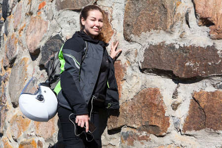 Portrait of motorcyclist woman standing near stone wall in apparel, with backpack on her back and helmet attached to it Stock Photo