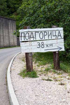 Wooden signpost with direction and distance to Podgorica city in countryside on rural asphalt road. Montenegro, Europe. Podgorica inscription in Montenegrin Standard-Bild - 121328537