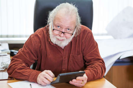 Portrait of European man with a beard holding a calculator in his hands, office room Imagens - 122403964