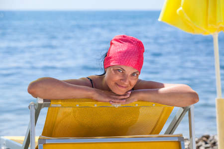 Young European woman gets suntan on sunbed near sea. Looking at camera and smiling 版權商用圖片
