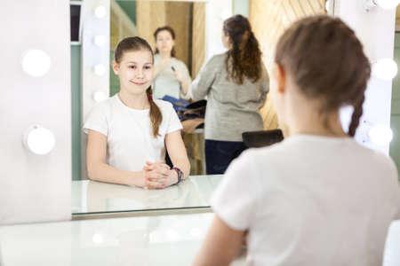 Mutter und Teenager-Mädchen, die sich auf das Fotoshooting in der Umkleidekabine vor dem breiten Spiegel vorbereiten