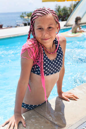 Teenager girl get out from swimming pool, dressed swimsuit and pink dreadlocks on head 免版税图像