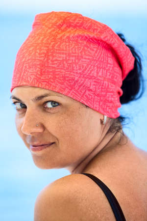 Facial portrait of beautiful tanned Caucasian woman with red headkerchief looking at camera against blue sea