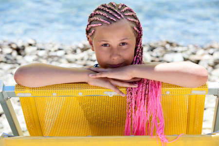 Facial portrait of pre-teen Caucasian girl with pink dreadlocks hairstyle looking out from yellow sun lounger, sunny coaside Foto de archivo