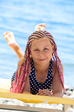Pretty Caucasian girl with pink dreadlocks hairstyle lying on yellow sunbed at sunny day, looking at camera