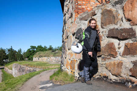 Motorcyclist woman travel on foot after leaving bike near atraction