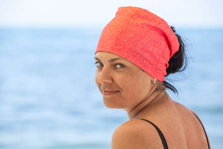 Portrait of beautiful tanned woman with red headkerchief looking at camera against blue sea, copy space Stock fotó - 122404212