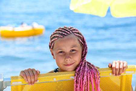 Face of happy pre-teen Caucasian girl with pink dreadlocks hairstyle looking out from yellow sun lounger, sunny coastline