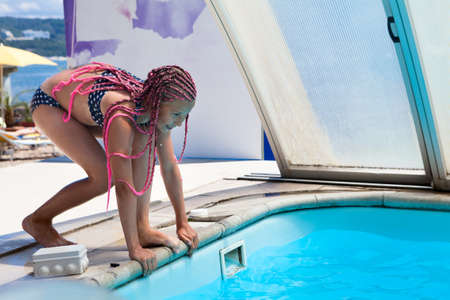 Athletic European teenager girl ready to jump into swimming pool from board, female with pink dreadlocks