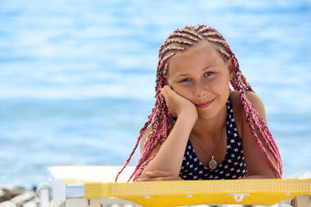 Portrait of preteen Caucasian girl with pink dreadlocks hairstyle tanning on beach on seacoast
