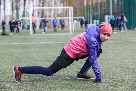 Eleven-year female football player does exercises for flexibility, warm-up before match 免版税图像
