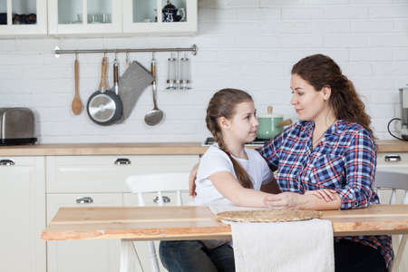 Adult mom has a serious conversation with her teenage daughter, talking at kitchen at table, copyspace