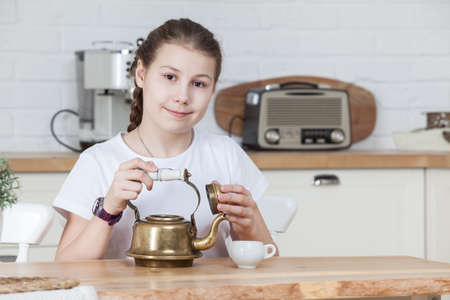 Twelve years old Caucasian girl holding teapot with opened cap in hands, looking at camera, kitchen interior
