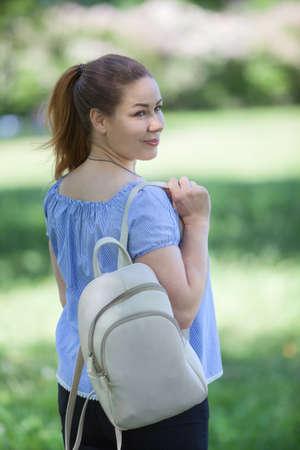 Rear view at pleasured woman walking in summer park, beige backpack hanging on her shoulder