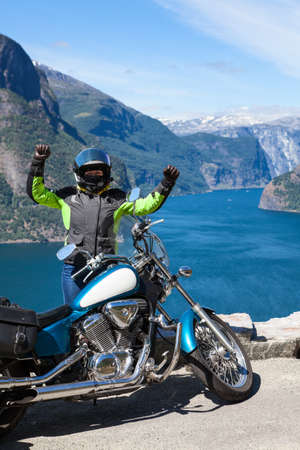 Excited woman motorcyclist glads to travel by motorcycle in Norway, Scandinavia. Viewpoint with Northern sea and fjords. Sogn og Fjordane