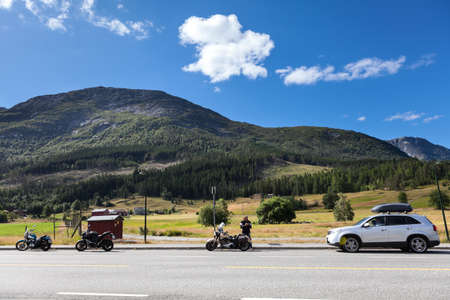 Three motorcycles and car standing on roadside of highway in mountains of Norway. Travel in Scandinavia by vehicles. Europe
