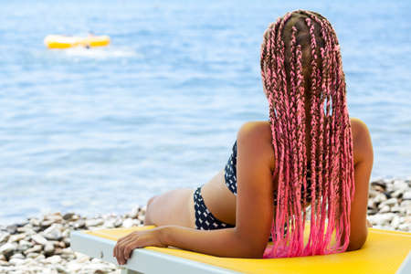 Rear view of pretty girl with pink African braids lying back on yellow sun lounger on coastline 스톡 콘텐츠