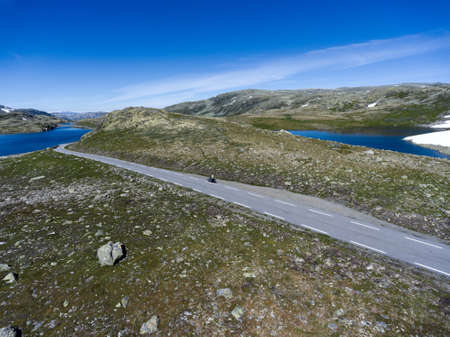 Motorcycle driving on asphalt road in Norwegian highlands. Snow road Aurlandsvegen is in the Aurland, Norway