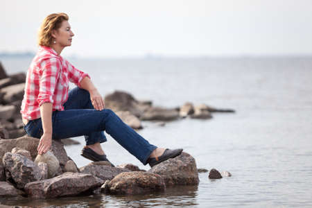 Caucasian woman sitting on stone near the water. Contemplates grey ocean on the background. Copy space