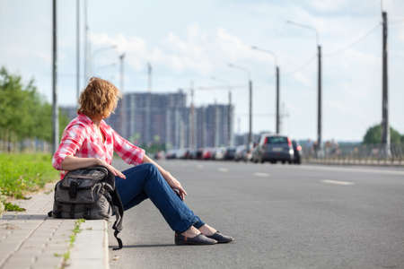 Woman waiting vehicle for hitchhiking, urban roadside, copy space, summer season, empty road Stock Photo