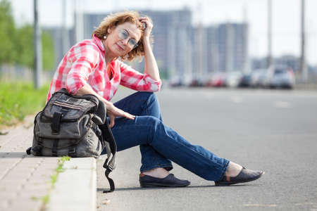 Caucasian woman hitch a ride, alone traveller sitting on roadside and waiting the car