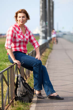 Mature Caucasian woman with backpack sitting on city street, resting walker