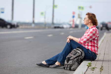 Mature European woman hitchhiker sitting on roadside and waiting the car