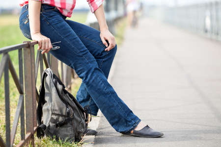 Unrecognizable European female sitting on steel fence of pedestrian pathway with urban backpack on earth