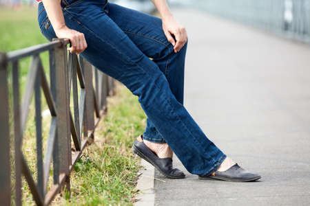 Unrecognizable Caucasian female sitting on steel fence of pedestrian pathway, blue jeans and comfortable shoes Stock Photo