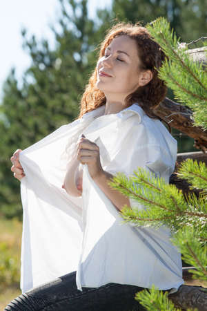 Pretty woman with unbuttoned shirt and in sunny meadow in forest