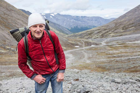 Happy and smiling mature backpacker looking at camera while hiking in mountains