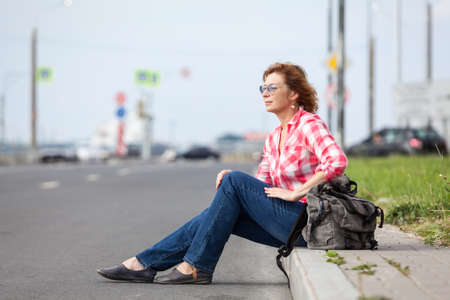 Mature Caucasian woman in eyeglasses sitting on road curb and hitchhiking, waiting the car
