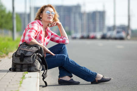 Caucasian woman hitch a ride on empty asphalt road, alone traveler sitting on roadside and waiting the car